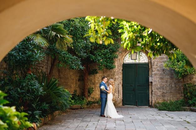 De bruid en bruidegom staan knuffelend in de coutryard in het oude centrum van perast