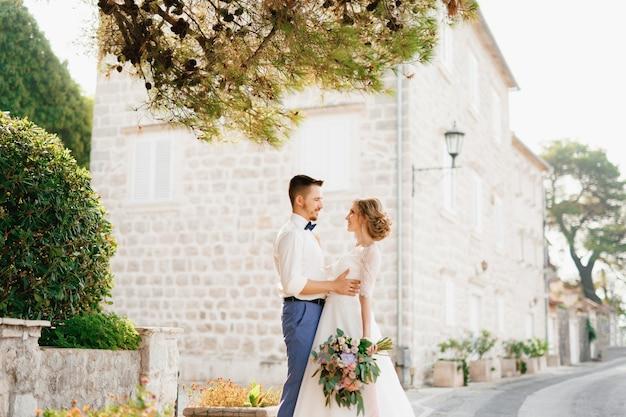 De bruid en bruidegom staan knuffelend onder de dennentakken in de buurt van een prachtig bakstenen huis