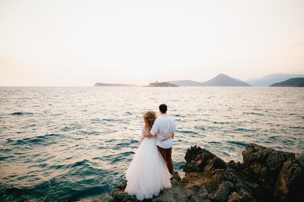 De bruid en bruidegom staan knuffelend op de rotsen bij de zee en kijken in de verte