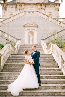 De bruid en bruidegom staan knuffelend op de trappen van de geboorte van de heilige maagd maria-kerk in