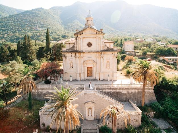 De bruid en bruidegom staan knuffelend op de trappen van de kerk van de geboorte van de heilige maagd maria