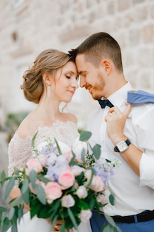 De bruid en bruidegom staan knuffelende handen in de buurt van een prachtig bakstenen huis in het oude centrum van perast