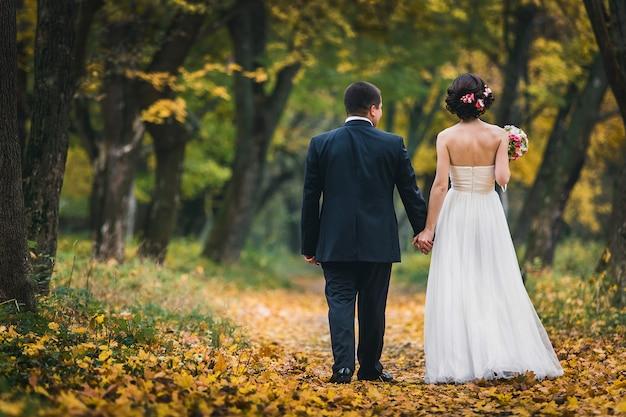 De bruid en bruidegom staan met hun rug elkaar de hand vasthouden en wandelen in het park