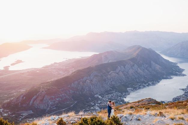 De bruid en bruidegom staan naast de houten bank op de top van de berg lovcen met uitzicht op de baai van