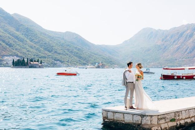 De bruid en bruidegom staan naast elkaar op de pier in de baai van de kotor-eilanden van perast