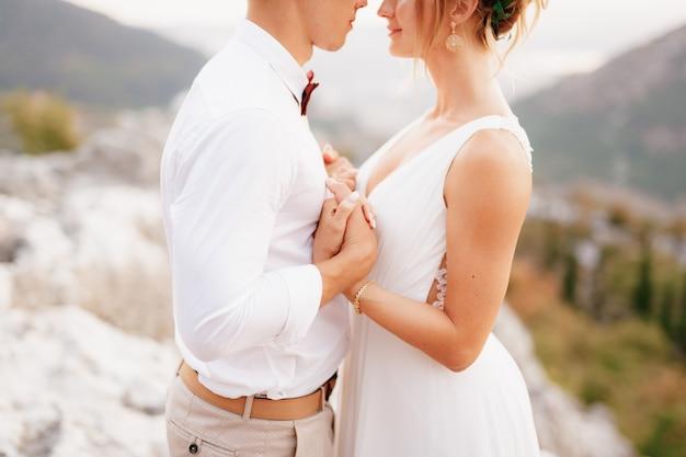 De bruid en bruidegom staan omhelzend tussen de bergen, hand in hand en kijken elkaar close-up aan