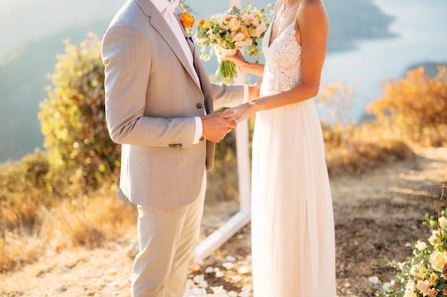 De bruid en bruidegom staan op de berg lovcen bij de huwelijksboog en houden elkaars hand vast