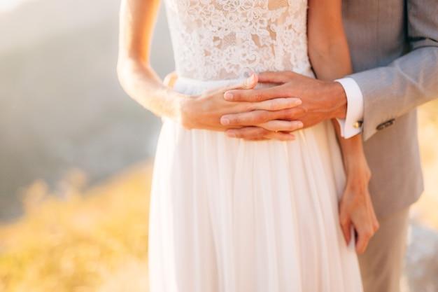 De bruid en bruidegom staan op de berg lovcen knuffelen en houden elkaars handen vingers gekruist close-up