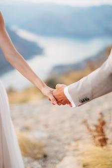 De bruid en bruidegom staan op de berg lovcen met uitzicht op de baai van kotor en houden elkaars hand vast