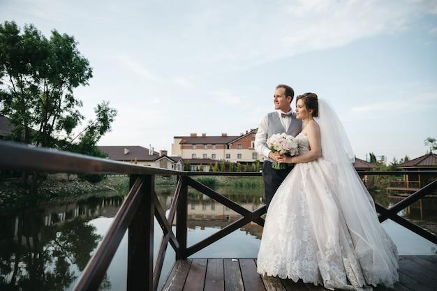De bruid en bruidegom staan op de brug en kijken weg