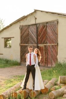 De bruid en bruidegom staan op de logs en knuffelen tegen de achtergrond van een oude schuur.