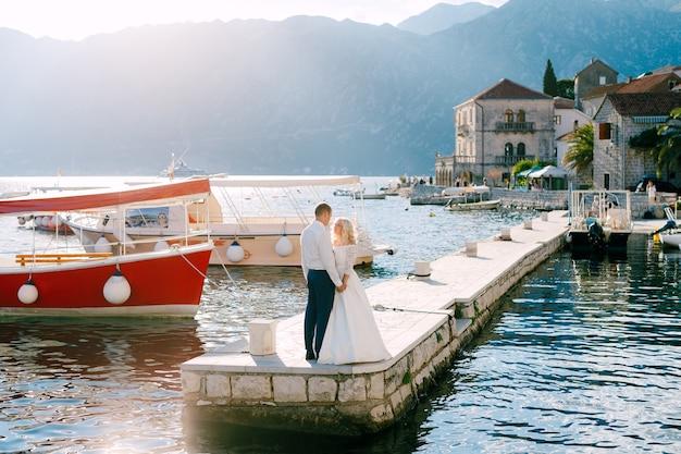 De bruid en bruidegom staan op de pier bij perast hand in hand en kijken elkaar in de ogen
