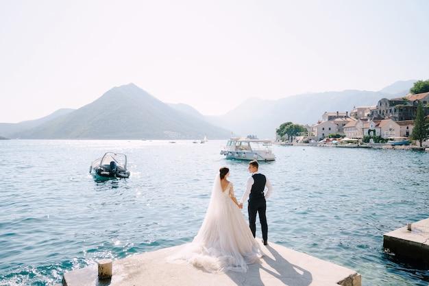 De bruid en bruidegom staan op de pier in de baai van kotor en kijken elkaar tegen de