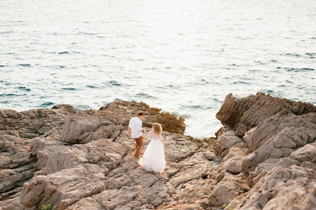 De bruid en bruidegom staan op de rotsen bij de zee en kijken elkaar aan