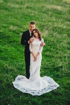 De bruid en bruidegom staan op een heuvel
