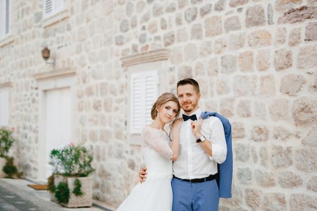 De bruid en bruidegom staan te knuffelen in de buurt van een prachtig bakstenen huis in het oude centrum van perast de bruid