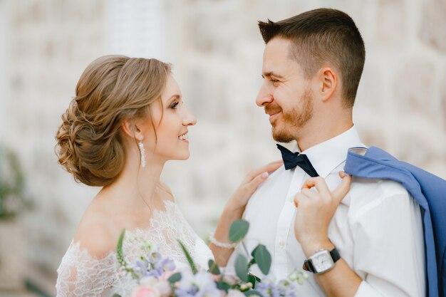 De bruid en bruidegom staan te knuffelen in de buurt van een prachtig bakstenen huis