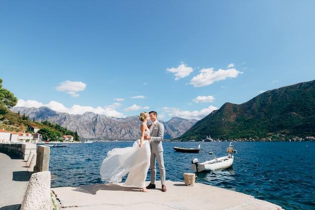 De bruid en bruidegom staan te knuffelen op de pier in de baai van kotor