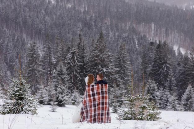 De bruid en bruidegom staan tegen de achtergrond van de bergen en knuffelen onder een kleed om warm te blijven. winter bruiloft