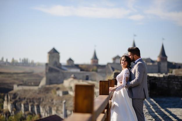 De bruid en bruidegom staan tegen de achtergrond van een oud kasteel. de bruidegom omhelst de bruid van achteren van achteren