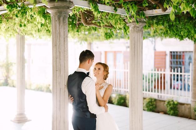 De bruid en bruidegom staan tussen de kolommen onder prachtige groene liaan in de oude stad