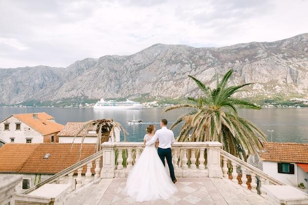 De bruid en bruidegom staan voor hen op de trap in de oude stad