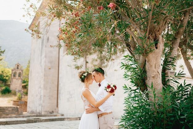 De bruid en bruidegom teder knuffelen in de buurt van de bloeiende oleanderstruik in de buurt van de oude kerk in