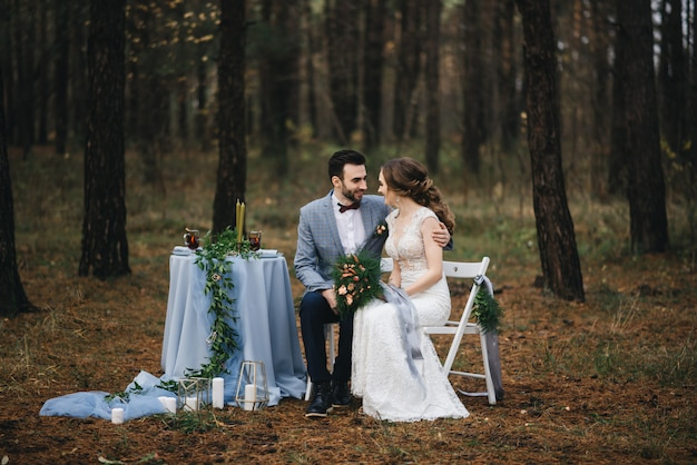 De bruid en bruidegom zitten aan een tafel voor twee in het bos. herfst. het concept van een romantische date