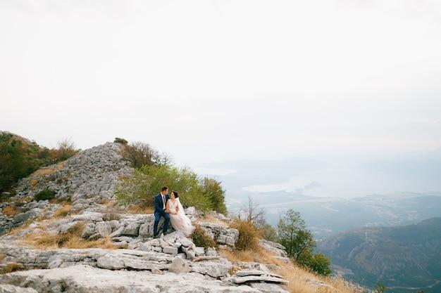 De bruid en bruidegom zitten elkaar omhelzend op een rots op de berg lovcen