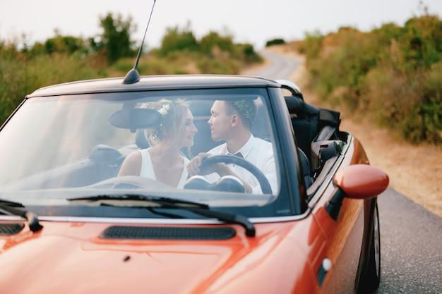 De bruid en bruidegom zitten in een auto op de snelweg in de bergen