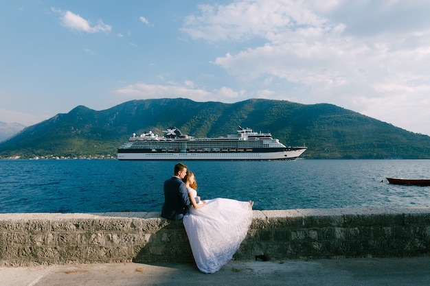 De bruid en bruidegom zitten knuffelend op een stenen hek van de pier, de bruid leunt op de