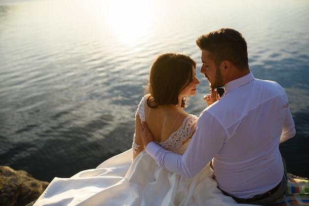 De bruid en bruidegom zitten op de rand van een klif tegen de achtergrond van het meer