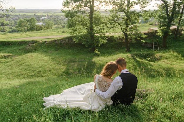 De bruid en bruidegom zitten op het groene gras. Premium Foto