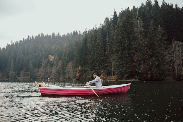 De bruid en bruidegom zitten samen in kleine roze boot op het meer. echtgenoot rolt zijn vrouw op de boot.