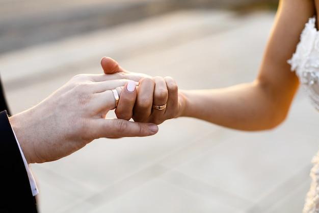 De bruid en de bruidegom houden elkaar handen met trouwringen