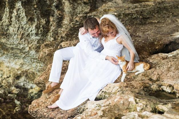 De bruid en de bruidegom strijken in openlucht een kat
