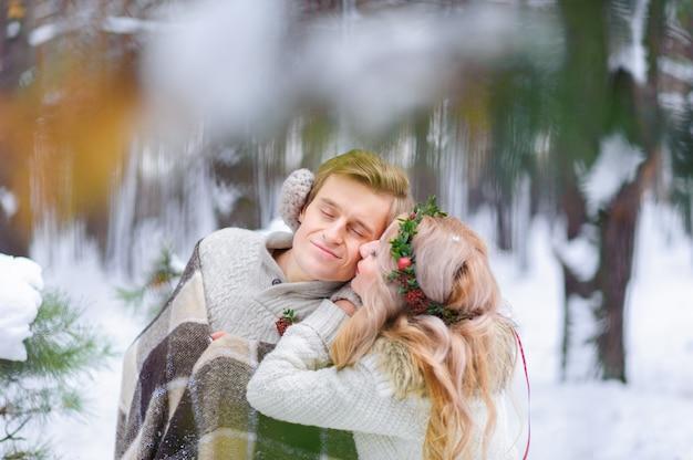 De bruid en de bruidegom zitten op login het de winterbos. detailopname. winter huwelijksceremonie.