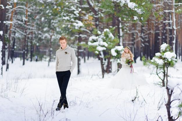De bruid en de bruidegom zitten op login het de winterbos.