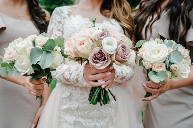 De bruid en de bruidsmeisjes houden handboeketten van pastelroze bloemen en greens vast