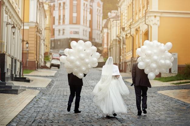 De bruid en vrienden gaan in de verte met een enorm aantal ballonnen