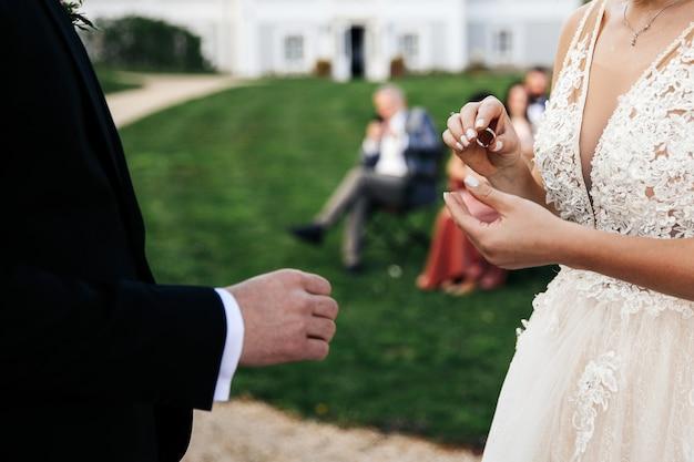 De bruid gaat de trouwring om de vinger van de bruidegom plaatsen