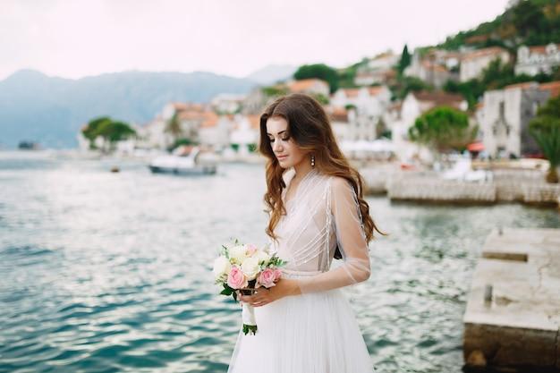 De bruid heeft een boeket rozen in haar handen en staat op de pier bij het oude centrum van perast