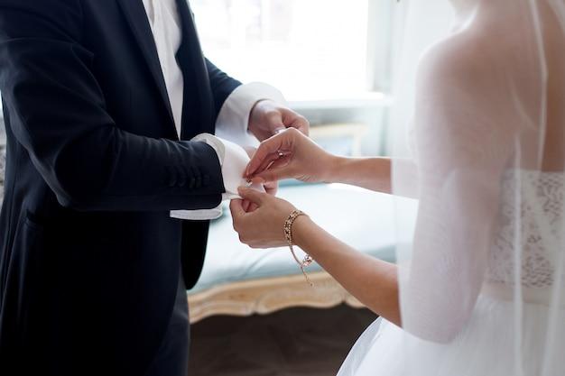 De bruid helpt haar verloofde om manchetknopen vast te maken. bruiloft zorgen