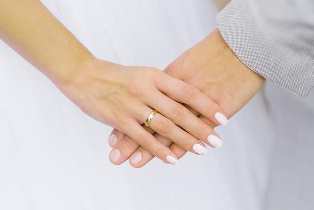 De bruid houdt de hand van de bruidegom vast. bruiloft verlovingsring aan je vinger