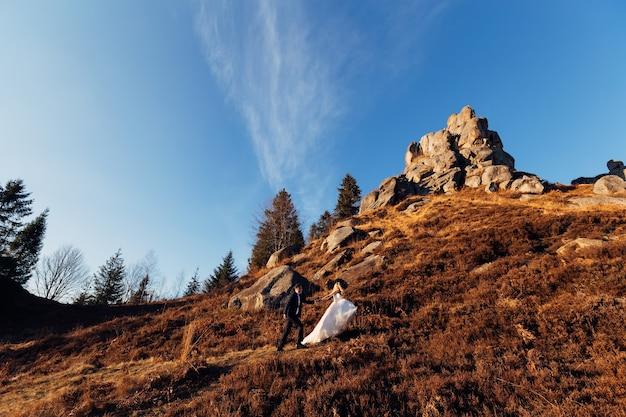 De bruid houdt de hand van de bruidegom vast en ze gaan de heuvel op met klifnatuur