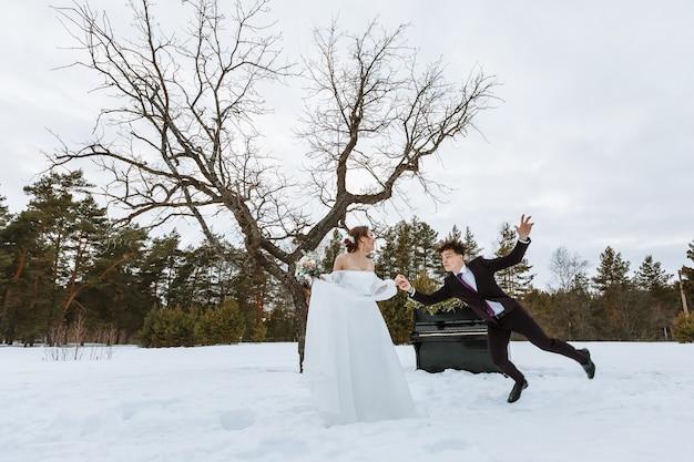 De bruid houdt de hand van de bruidegom vast. winterbos, met een piano op de achtergrond. de bruidegom gleed uit