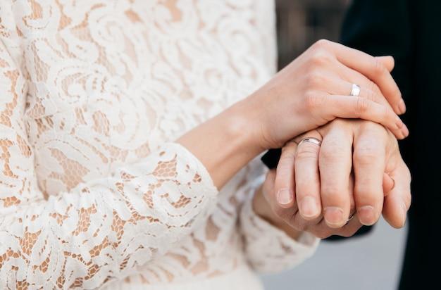 De bruid houdt de handen van de bruidegom vast