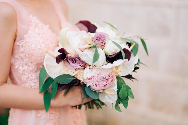 De bruid houdt een boeket rozen, calla lelies, pioenrozen en eucalyptustakken vast.