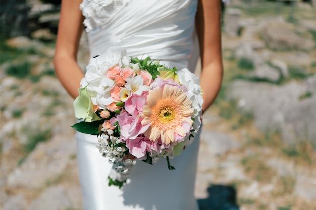 De bruid houdt een boeket van verse lente en zomerbloemen in pastelkleuren op een vage achtergrond, selectieve nadruk