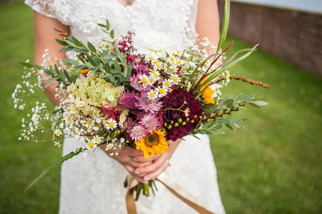 De bruid houdt een boeket verse lente- en zomerbloemen vast